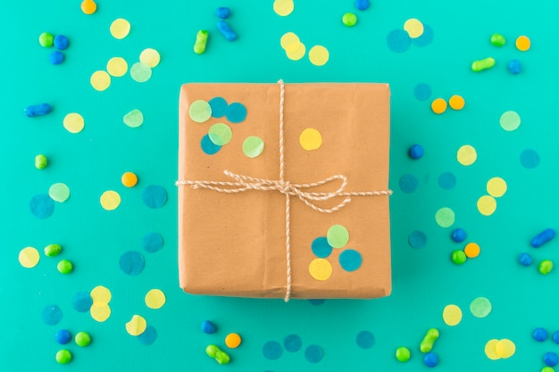 Wrapped birthday gift surrounded with candies and confetti on green surface