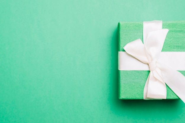 Wrapped birthday present with white ribbon bow on green background