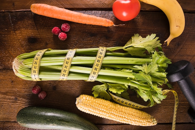 Wrapped celery with vegetables and fruits on wooden table
