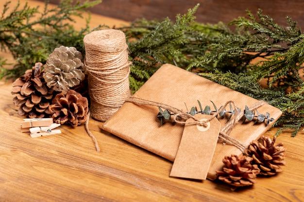 Завернутый рождественский подарок и сосновые шишки