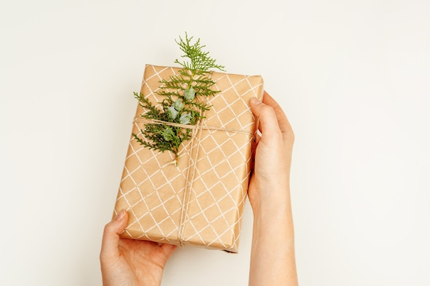 Wrapped christmas gift in woman hands above white background