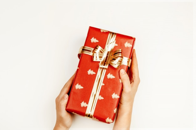Wrapped christmas gift in woman hands above white