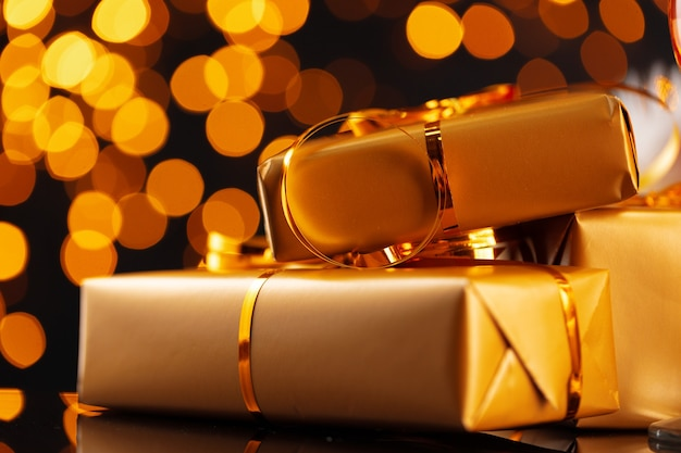 Wrapped christmas gifts on golden lights bokeh background close up