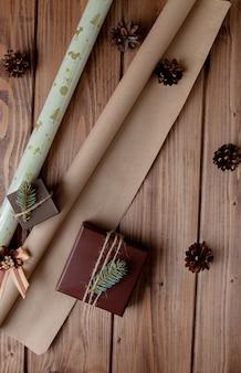 木製のテーブルにクラフト紙で包まれたクリスマスプレゼント。ギフト包装のプロセス。ライフスタイルの背景。上からの眺め。クリスマスのコンセプト。