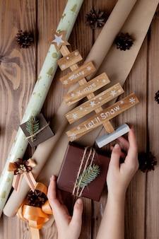 木製のテーブルにクラフト紙で包まれたクリスマスプレゼント。ギフト包装のプロセス。ライフスタイル