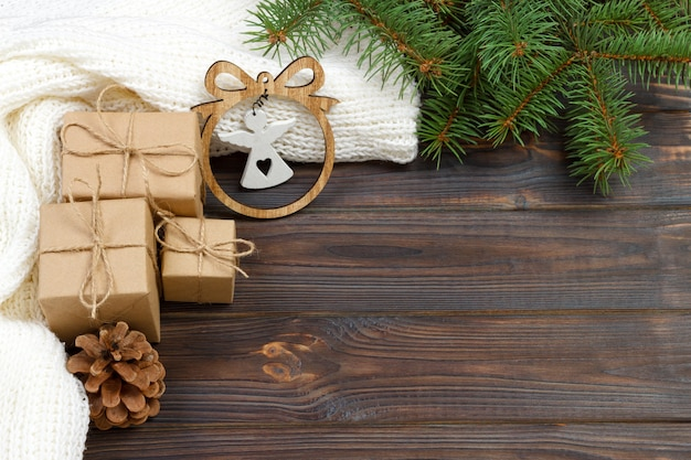 Wrapped christmas gifts with white angel on dark rustic wooden table with pine cones and fir branches. with copy space for your text.