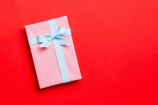Завернутый подарок на рождество или другой праздник ручной работы в бумаге с голубой лентой на красном фоне