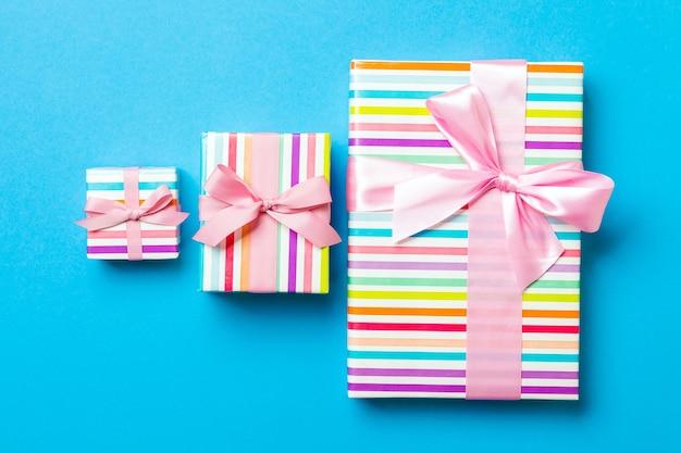 파란색 표면에 분홍색 리본이 달린 종이에 크리스마스 또는 다른 휴일 수제 선물 포장.