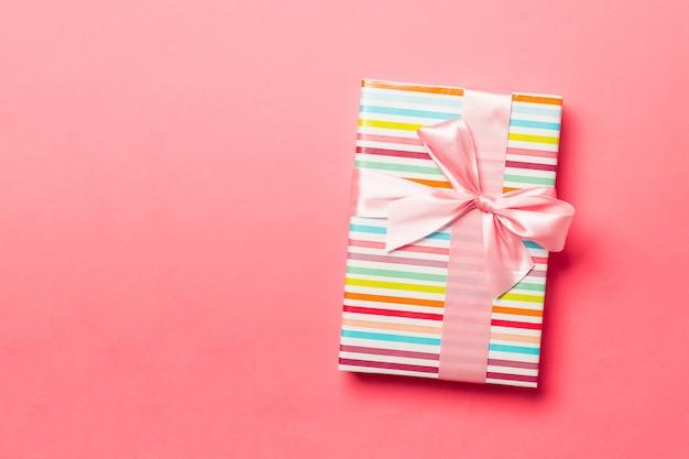 살아있는 산호 배경에 분홍색 리본이 달린 종이에 포장된 크리스마스 또는 기타 휴일 수제 선물. 선물 상자, 컬러 테이블에 선물 장식, 복사 공간이 있는 위쪽 전망.