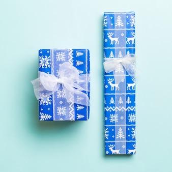 포장된 크리스마스 또는 기타 휴일 수제 선물은 파란색 배경에 흰색 리본이 있는 종이에 있습니다. 선물 상자, 컬러 테이블에 선물 장식, 위쪽 전망.