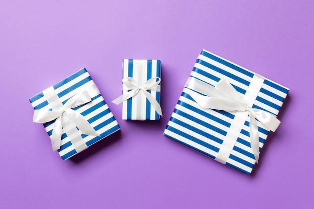 포장된 크리스마스 또는 기타 휴일 수제 선물은 보라색 배경에 흰색 리본이 있는 종이에 있습니다. 선물 상자, 컬러 테이블에 선물 장식, 위쪽 전망.