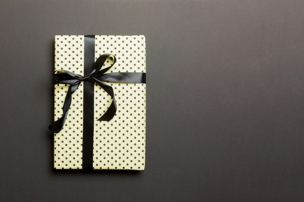 Wrapped christmas or other holiday handmade present in paper with black ribbon on black background