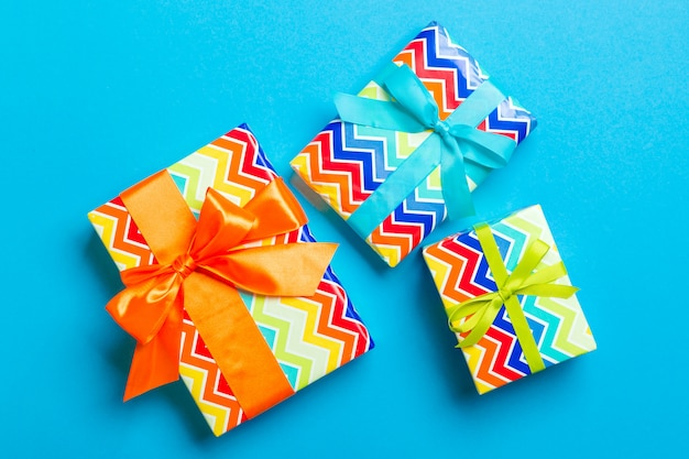 Wrapped christmas or other holiday handmade present in paper with blue, green and orange ribbon on blue background