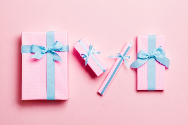 Wrapped christmas or other holiday handmade present in paper with blue ribbon on pink background