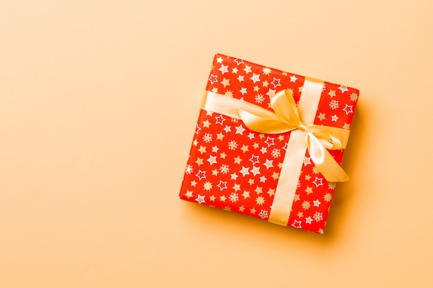 Wrapped christmas or other holiday handmade present in paper with gold ribbon on orange background