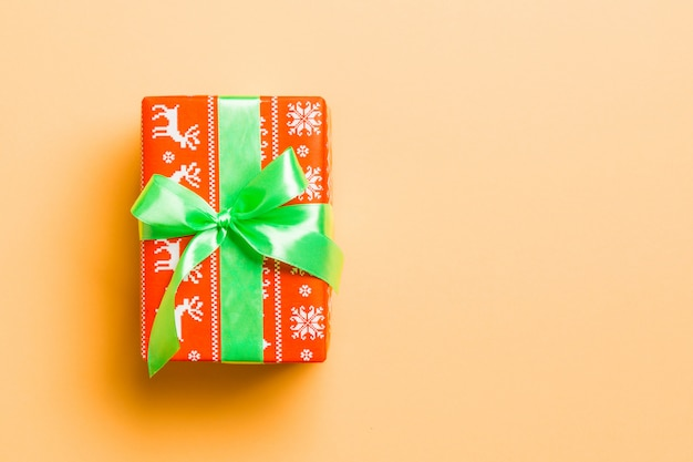 Wrapped christmas or other holiday handmade present in paper with green ribbon on orange background