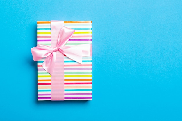 Wrapped christmas or other holiday handmade present in paper with pink ribbon on blue background