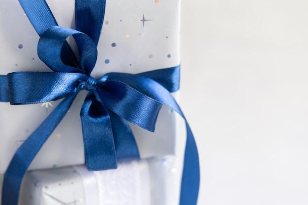 Обернутый рождественский подарок с бантом из голубой ленты крупным планом серо-синяя зимняя композиция