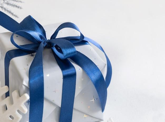 Обернутый рождественский подарок с бантом из голубой ленты крупным планом