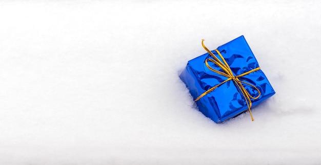 ゴールドのリボンで包まれたクラシックな青いギフトボックスは、白い雪の中にあります。お祝いの背景。
