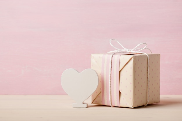 Wrapped gift box and heart decoration on pink wooden background