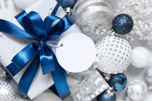 Упакованная подарочная коробка с синим бантом и круглой бумажной подарочной биркой на белом столе с белыми и серебряными рождественскими украшениями вокруг вида сверху. зимняя композиция с пустой этикеткой, макет, копией пространства
