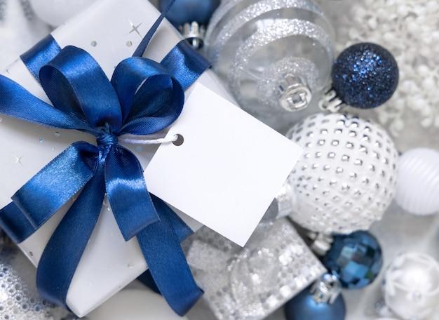 Упакованная подарочная коробка с синим бантом и квадратной бумажной подарочной биркой на белом столе с белыми и серебряными рождественскими украшениями вокруг вида сверху. зимняя композиция с пустой этикеткой, макет, копией пространства