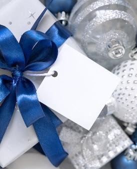 Упакованная подарочная коробка с синим бантом и квадратной бумажной подарочной биркой с рождественскими украшениями