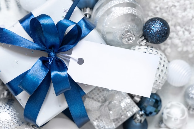 Wrapped gift box with a blue bow and paper gift tag on a white table with white and silver christmas decorations around top view. winter composition with blank label card, mockup, copy space