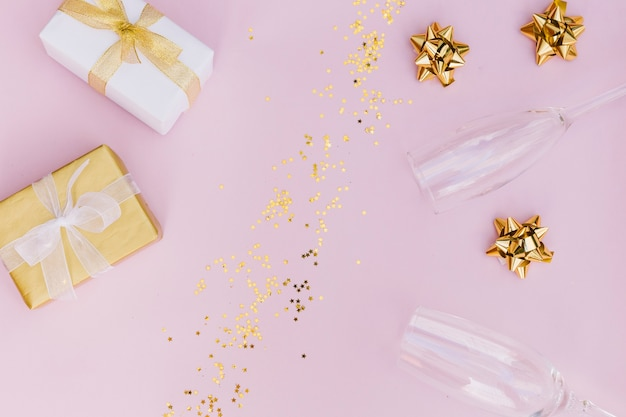 Wrapped gift box with bow; golden confetti; bow and champagne glasses on pink background