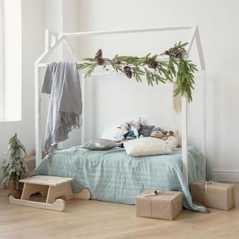 Упакованные подарочные коробки рядом с детской кроваткой в форме дома, украшенной к рождественским праздникам
