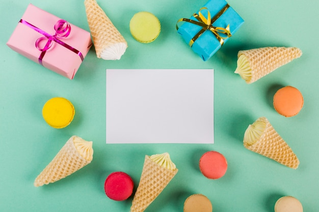 Wrapped gift boxes; macaroons and waffle with aalaw around the white paper on mint green backdrop