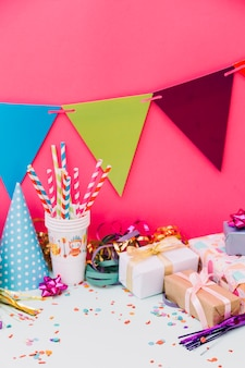 Wrapped gift boxes; party hat; streamers; ribbon bows and buntings against pink background
