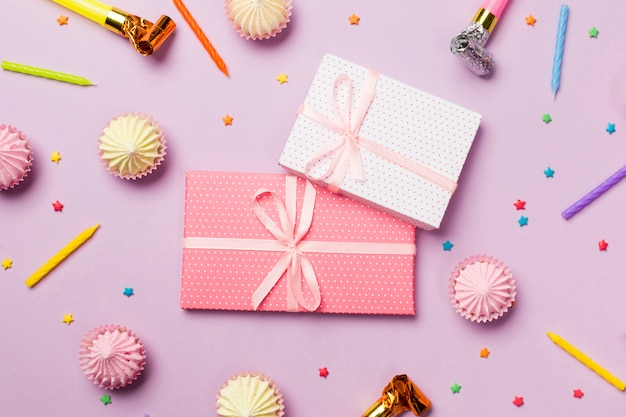 Wrapped gift boxes surrounded with candles; party horn; sprinkles; gift boxes; aalaw on pink background