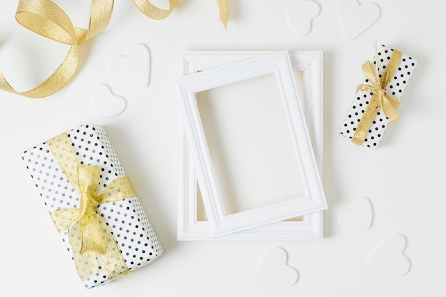 Wrapped gift boxes with heart shapes and wooden frames for wedding on white backdrop