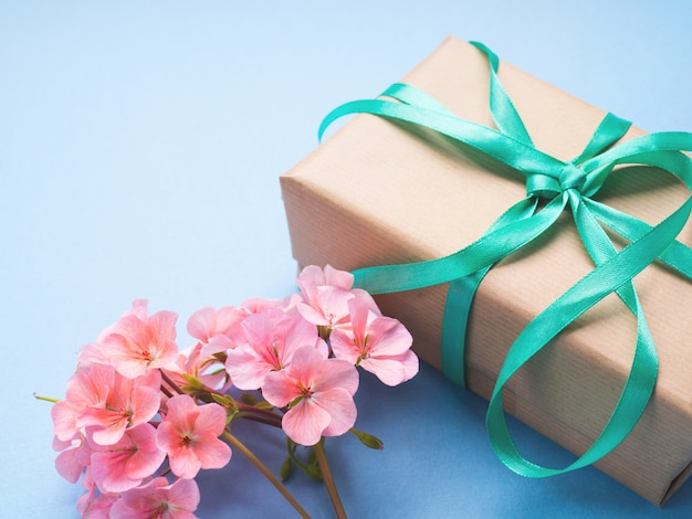 Wrapped gift and flowers flat lay