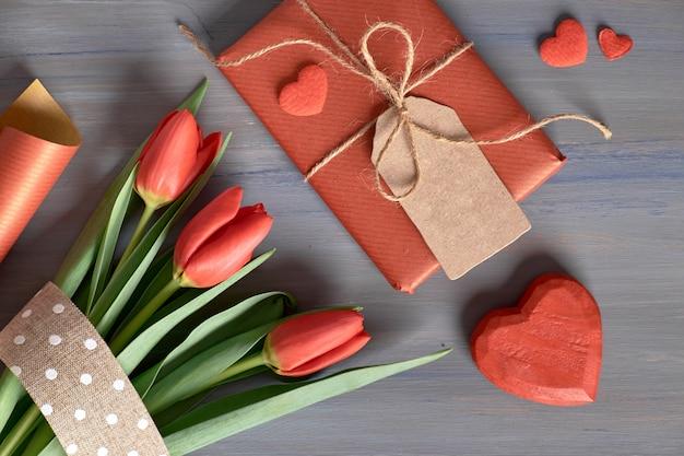 ラップされたギフトの赤いチューリップ、包装紙、木製のテーブルの装飾的な心