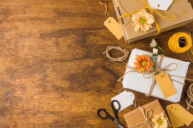 空のタグと木製のテーブルの上の美しい花で包まれたギフト 無料写真