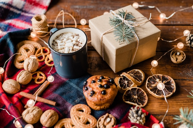 Упакованная подарочная коробка с хвойным деревом и узлом сверху, окруженная горячим напитком, палочками корицы, грецкими орехами, дольками лимона и печеньем.