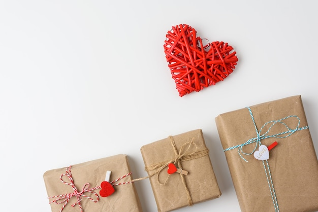 Wrapped gifts in brown paper and a red wicker heart on a white background, top view. valentine's day surprise