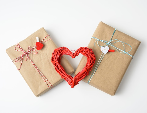 Wrapped gifts in brown paper and a red wicker heart on white, top view. valentine's day surprise