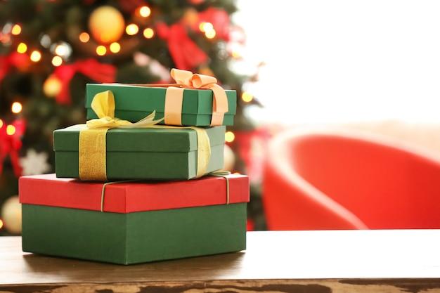 Обернутые подарки на столе против размытой рождественской елки. день подарков