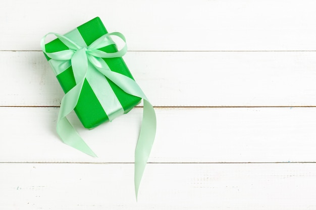 Wrapped gifts with ribbon on white wooden background top view