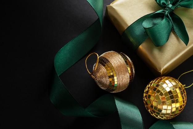 어두운 표면에 녹색 나비와 싸구려 포장 된 황금 선물