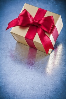 Wrapped golden giftbox with red ribbon bow top view