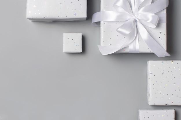 Упакованные серые подарочные коробки с белой лентой