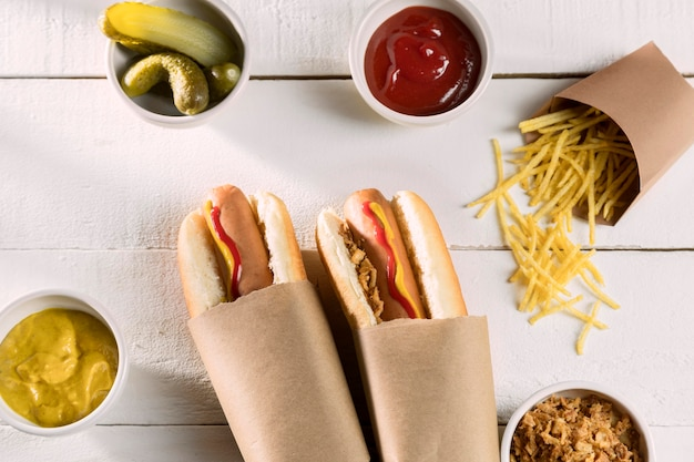 Wrapped hot dog with pickles and condiments