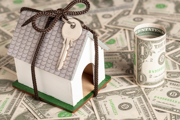 Wrapped house with keys on money background