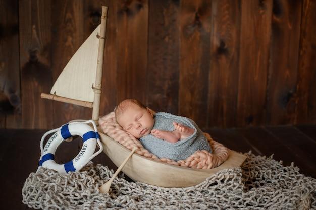 Обернутый в синюю ткань новорожденный спящий ребенок лежит в деревянной парусной лодке