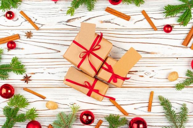 Обернутый подарок на деревянном фоне с рождественскими украшениями, вид сверху